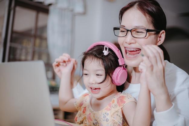Een moeder draagt een koptelefoon voor haar dochter om haar te helpen online te studeren