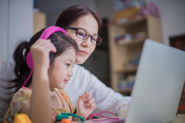 Een moeder draagt een koptelefoon voor haar dochter om haar te helpen online te studeren.