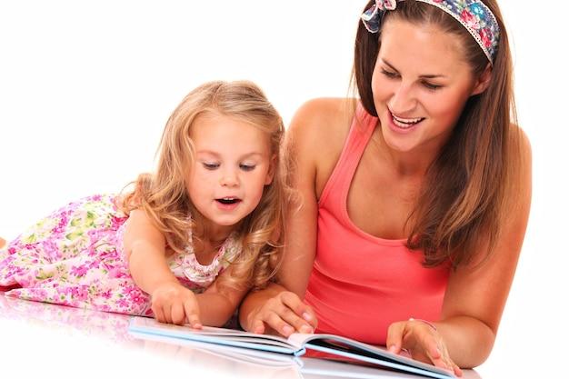 Een moeder en dochter die een boek over wit lezen