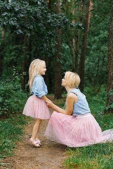 Een moeder en een dochter in dezelfde romantische kleren wandelen in het bos