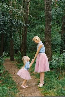 Een moeder en een dochter van vijf in dezelfde kleren die in het park of in het bos lopen