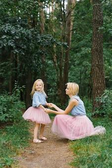 Een moeder en een dochter van vijf in dezelfde romantische kleren lopen in het park