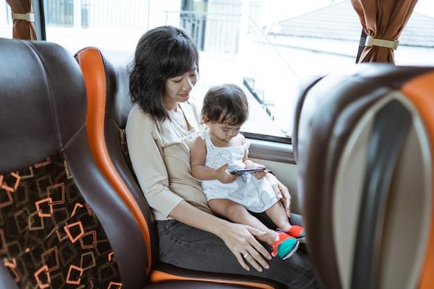Een moeder en een klein meisje houden een mobiele telefoon vast terwijl ze bij het raam in de bus zitten