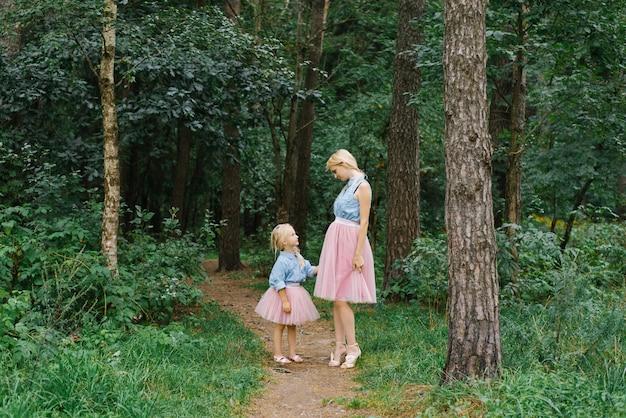 Een moeder en een vijfjarige dochter in dezelfde romantische kleding lopen in het park of in het bos. gelukkige jeugd en moederschap