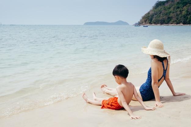 Een moeder en een zoon ontspannen en zittend op het strand en de zee in openlucht bij blauwe hemel