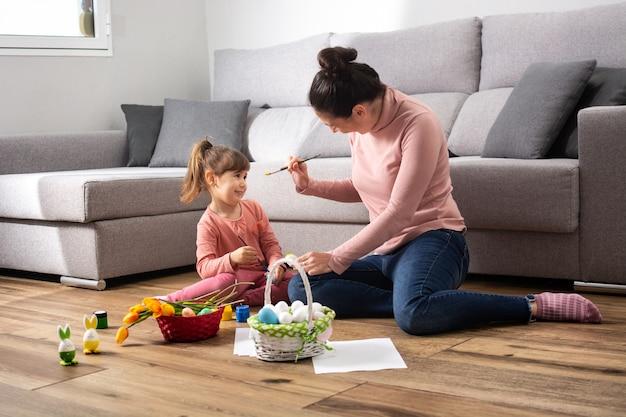 Een moeder en haar dochter die thuis paaseieren schilderen.