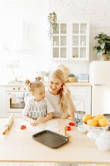 Een moeder en haar dochtertje bereiden samen het bakken van deeg in hun keuken thuis.