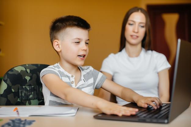 Een moeder en haar kind zijn thuis achter de computer bezig met afstandsonderwijs. blijf thuis, training.