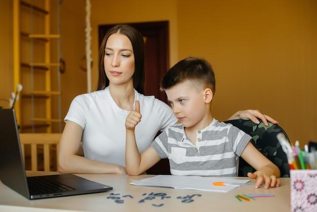 Een moeder en haar kind zijn thuis achter de computer bezig met afstandsonderwijs