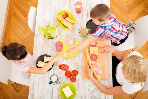 Een moeder en haar kinderen ontbijten thuis.