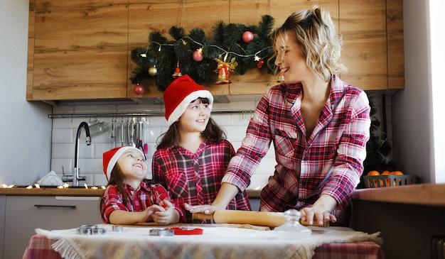 Een moeder en twee jonge dochters in rode geruite overhemden en rode hoeden leren koekjes maken in de keuken die is ingericht voor kerstmis