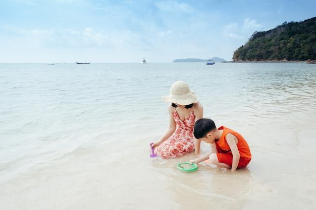 Een moeder en zoon op strand buitenshuis zee en blauwe lucht