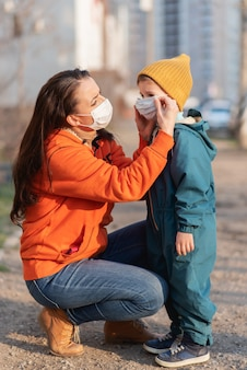 Een moeder helpt buiten bij het dragen van een medisch masker voor haar kind tijdens de coronavirus pandemie en covid -19.