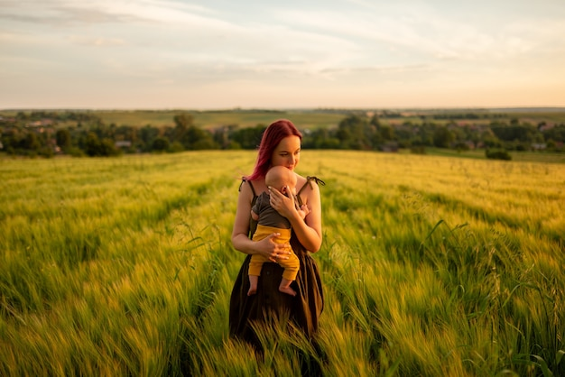 Een moeder houdt teder haar drie maanden oude zoon in haar armen in een tarweveld.