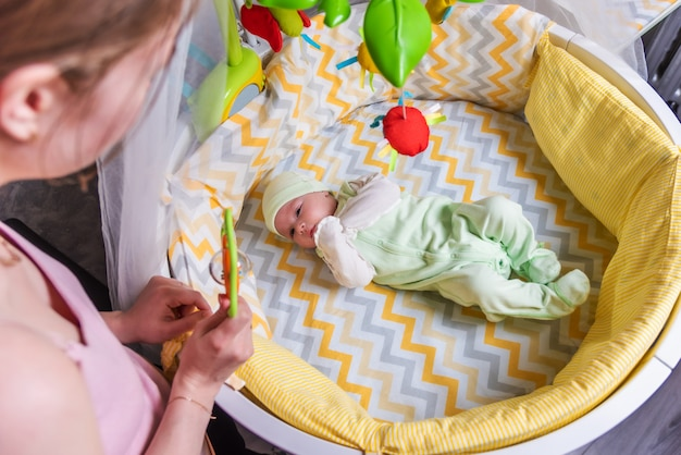 Een moeder kijkt naar haar pasgeboren baby die in een wieg ligt