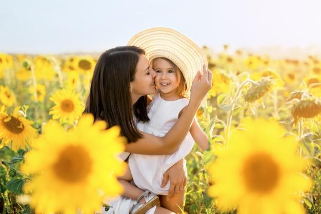 Een moeder knuffelt en kust haar dochter liefdevol bij zonsondergang in een veld met zonnebloemen