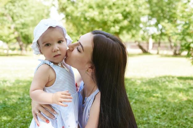 Een moeder kust een klein meisje.
