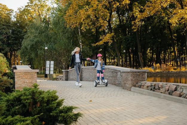 Een moeder leert haar dochtertje tijdens zonsondergang op een segway in het park te rijden. gelukkige familievakantie.