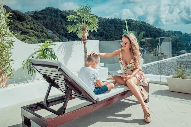Een moeder leest een boek voor aan haar zoon die op een zonnebank in het resort zit.