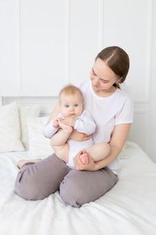 Een moeder met een baby in haar armen knuffelt zachtjes een kind op het bed thuis