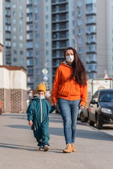 Een moeder met een baby in medische maskers loopt over straat tijdens de coronavirus pandemie en covid -19.