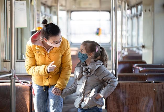 Een moeder met een kind in een leeg openbaar vervoer, met maskers op tijdens een pandemie coronavirus.