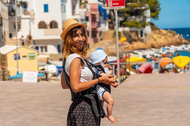 Een moeder met haar baby op het strand van sa tuna aan de kust van begur in de zomer, girona aan de costa brava van catalonië in de middellandse zee
