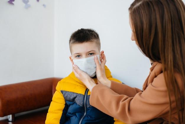 Een moeder met haar kind staat tijdens de quarantaine in een masker. pandemie, coronavirus