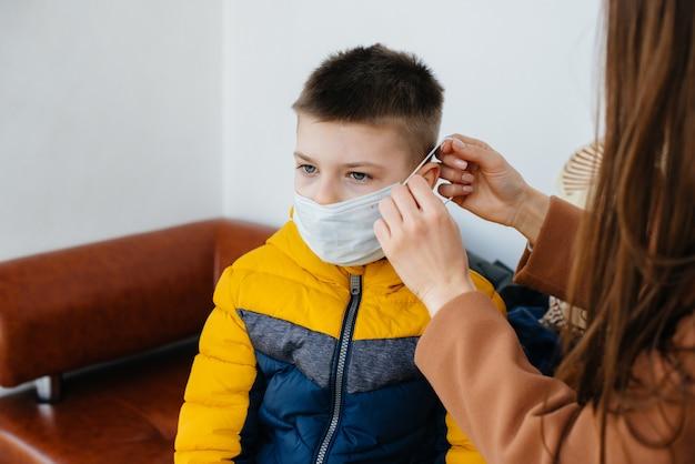 Een moeder met haar kind staat tijdens de quarantaine in een masker. pandemie, coronavirus.