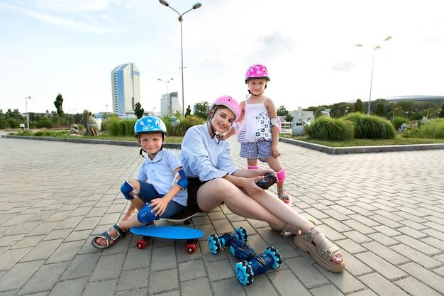 Een moeder met kinderen in helmen zit op een skateboard en speelt in het park met een robotauto die bestuurd wordt door een handschoen.
