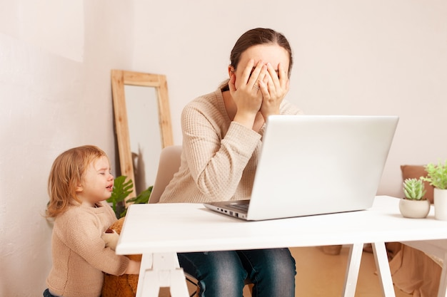 Een moeder met zwangerschapsverlof zit achter een laptop en werkt, een kind dat hysterisch huilt leidt af