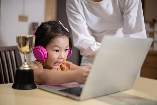 Een moeder opent een computer zodat haar dochter online kan studeren Premium Foto