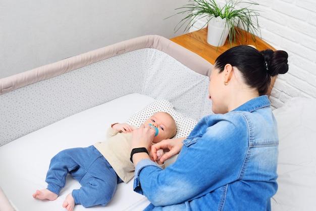 Een moeder speelt met een baby die in een zijbed voor een pasgeborene of in een moderne box ligt