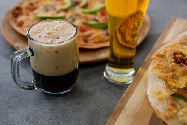 Een mok bier en glas met pizza op de achtergrond