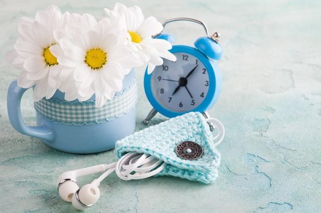 Een mok, blauwe wekker en bloemen