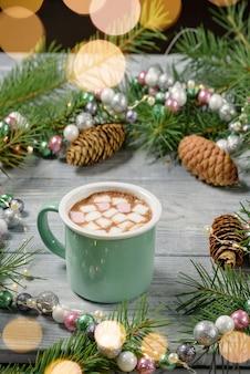 Een mok cacao met marshmallows op een tafel met kerstdecor gemaakt van dennentakken, slingers van donuts.