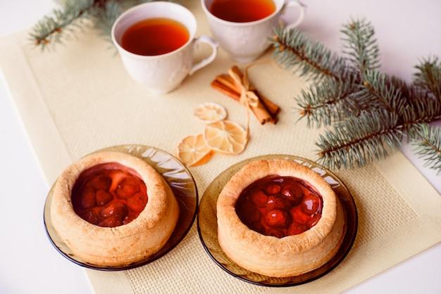 Een mok hete thee en cake. kerstkaart. de tak van de boom is vuren.
