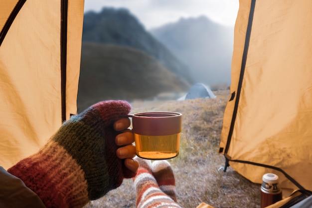 Een mok hete thee in de hand van een vrouw in een tent
