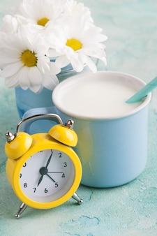 Een mok melk met stro, gele wekker en bloemen