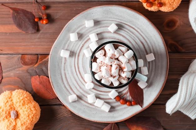 Een mok met cacao en marshmallows op een bord, pompoenen en een warme trui op een houten tafel. herfst warme dranken. bovenaanzicht. ruimte kopiëren