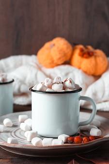 Een mok met cacao en marshmallows op een bord, pompoenen en een warme trui op een houten tafel. herfst warme dranken. verticale weergave