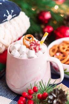 Een mok met marshmallow in de buurt van wintertruien schaal met pretzels kerst- en nieuwjaarsversieringen