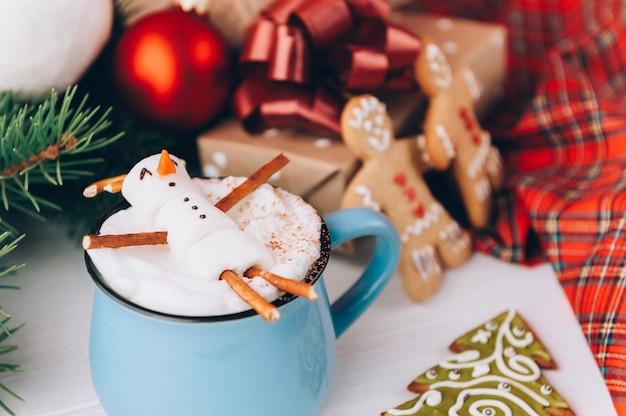Een mok met warme chocolademelk op een houten tafel met een marshmallow-man die in een mok rust