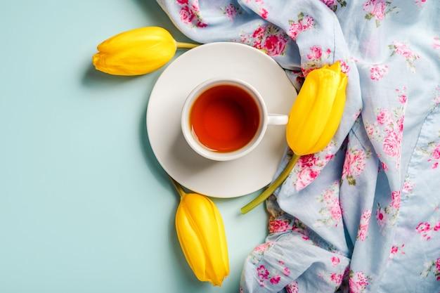 Een mok thee en gele tulpen op een blauwe achtergrond. de lentesamenstelling met bloemen
