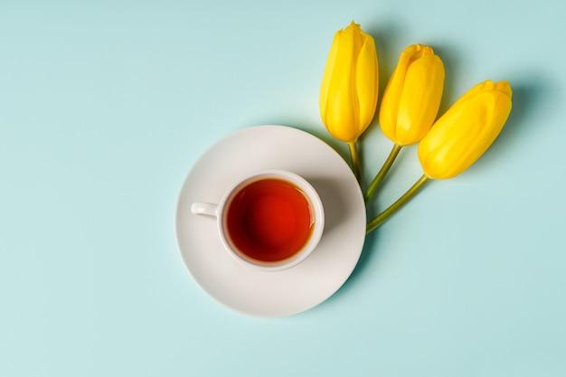 Een mok thee en gele tulpen op een blauwe achtergrond. de lentesamenstelling, plaats voor tekst