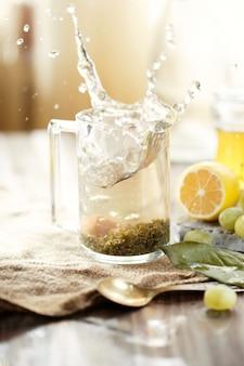 Een mok thee met grote spatten, citroen, druiven op de tafel