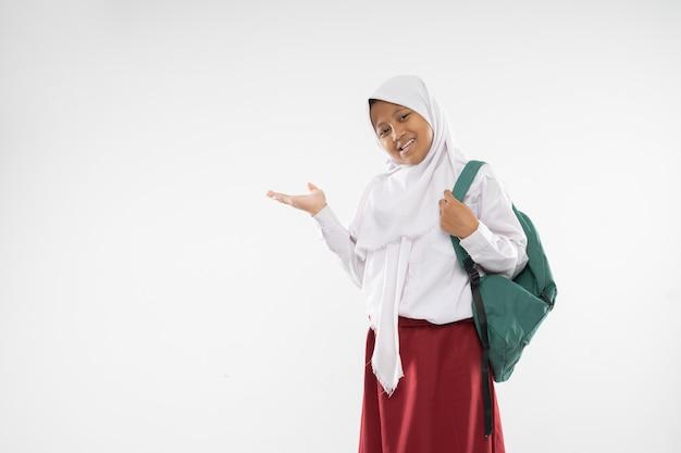 Een mollig meisje in een basisschooluniform met capuchon en handgebaren die iets aanbieden...