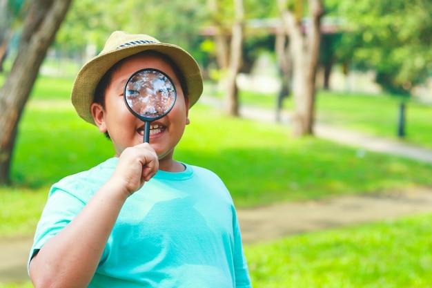 Een mollige jongen met een vergrootglas om kleine wezens in de natuur te bestuderen