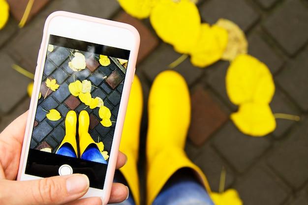 Een momentopname van de herfst op een smartphone. heldergele laarzen in gebladerte