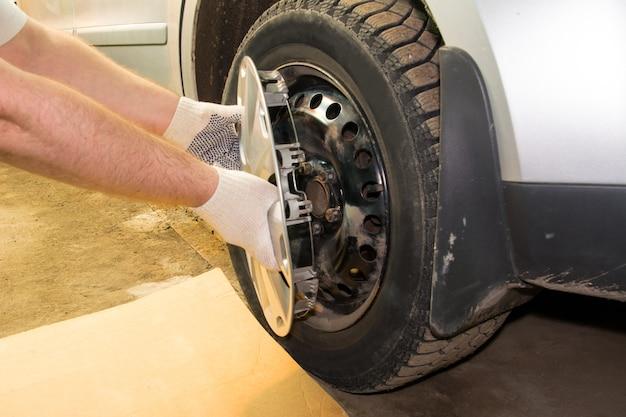 Een monteur die de wieldop van een autowiel verwijdert. banden monteren.